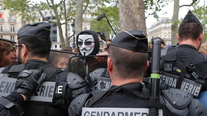 Riot police officers face anti-police protesters before a police gathering to denounce the almost daily violent clashes at protests against a labor reform, Wednesday, May 18, 2016. French police are taking to the streets to protest against what they describe as hatred directed at them. (AP Photo/Francois Mori)