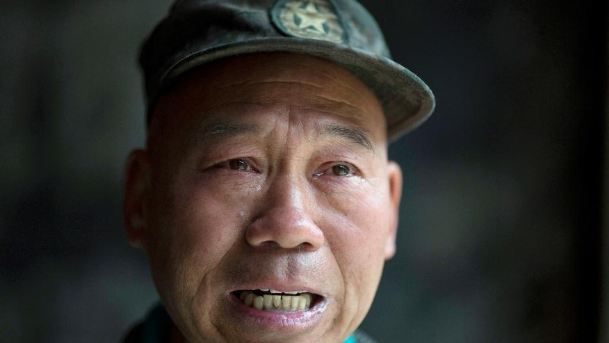 In this May 2, 2016 photo, Zhao Shunli tears up while talking about his struggles in Luoyang in central China's Henan province. Zhao's transformation takes place several times a week in a simple bedroom filled with Mao Zedong memorabilia, its concrete walls lined with posters portraying the founder of the communist state. Once his army jacket buttons up and his white gloves snap on, Zhao the garbage picker becomes Zhao the People's Liberation Army veteran. (AP Photo/Ng Han Guan)