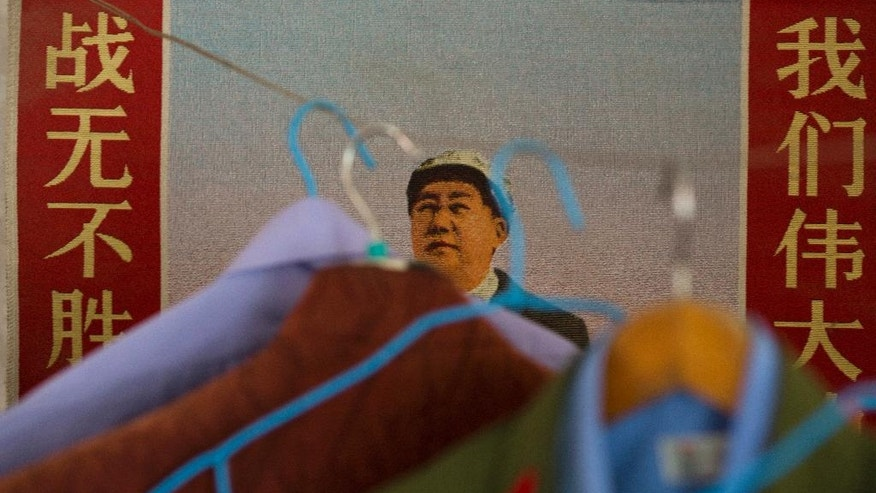 "In this May 2, 2016 photo, a poster of Mao Zedong with the words ""Undefeated in battle, our great leader"" is hung on the wall in Zhao Shunli's home in Luoyang in central China's Henan province. Zhao's transformation takes place several times a week in a simple bedroom filled with Mao Zedong memorabilia, its concrete walls lined with posters portraying the founder of the communist state. Once his army jacket buttons up and his white gloves snap on, Zhao the garbage picker becomes Zhao the People's Liberation Army veteran. (AP Photo/Ng Han Guan)"