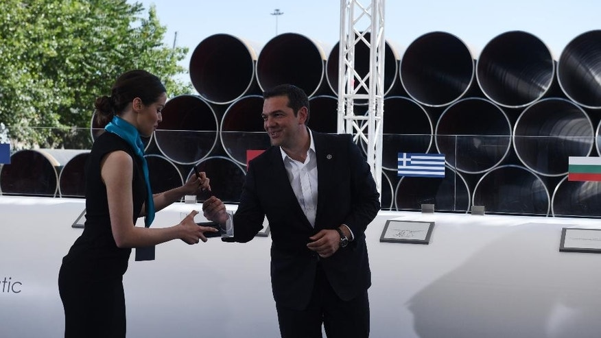 Greece's Prime Minister Alexis Tsipras prepares to sign during the Trans Adriatic Pipeline inauguration ceremony, in the northern Greek city of Thessaloniki, Tuesday, May 17, 2016. Construction work is starting on a new pipeline project bringing Azeri gas through northern Greece and Albania to Italy, and reducing Europe's energy dependency on Russia. First deliveries to Europe are expected in 2020. (AP Photo/Giannis Papanikos, Pool)