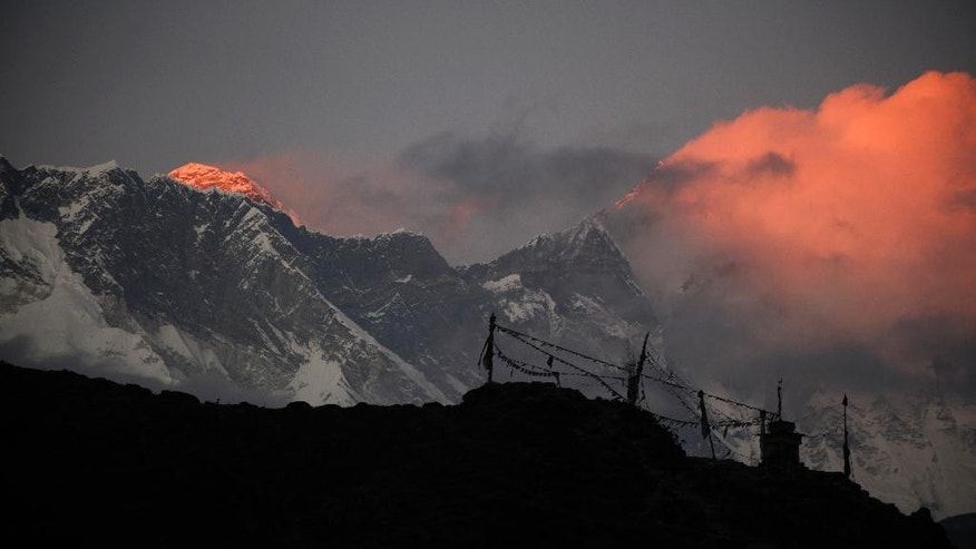 FILE - In this Saturday, Nov. 7, 2015 file photo, the last light of the sun sets on Mount Everest, as seen from Pangboche, Nepal.  High winds have delayed dozens of climbers trying to reach the summit of Mount Everest, a mountaineering official said Wednesday, May 18, 2016. The winds have made it difficult for the climbers to make their attempts for the summit but posed no immediate danger, said Gyanendra Shrestha, an official in Nepal's Mountaineering Department who is at base camp on Everest.(AP Photo/Tashi Sherpa, File)