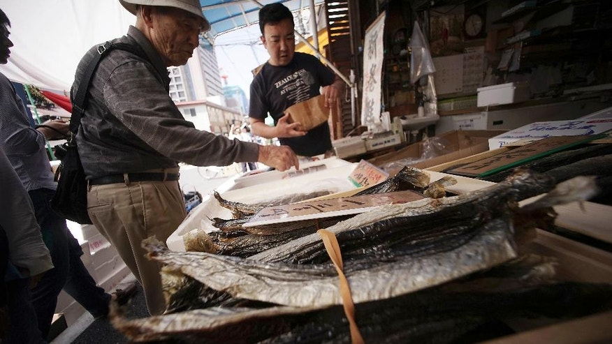 A man buys dried fish from a shop in Tokyo, Wednesday, May 18, 2016. Japan's economy grew at a better than expected 1.7 percent annual pace in the first quarter of this year, as solid consumer demand and higher government spending offset relatively weak business investment and sluggish exports. (AP Photo/Eugene Hoshiko)