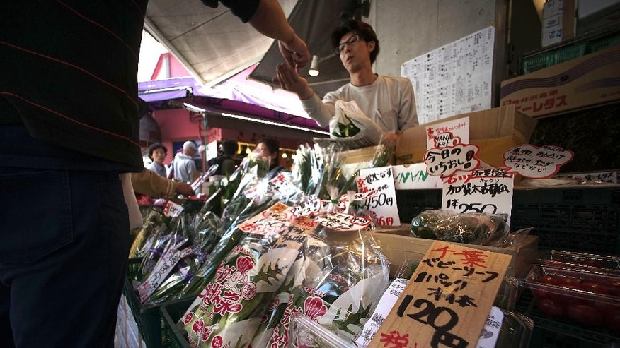 A man buys vegetable from a shop in Tokyo, Wednesday, May 18, 2016. Japan's economy grew at a better than expected 1.7 percent annual pace in the first quarter of this year, as solid consumer demand and higher government spending offset relatively weak business investment and sluggish exports. (AP Photo/Eugene Hoshiko)