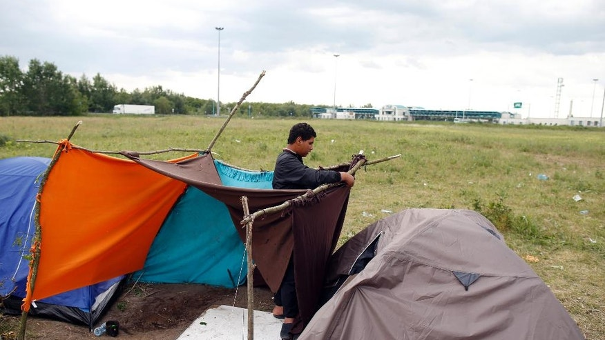 A man prepares his tent in the makeshift refugee camp near the Horgos border crossing into Hungary, near Horgos, Serbia, Wednesday, May 18, 2016. A small tent city has formed on Serbia's border with Hungary where migrants are waiting to cross into the European Union despite border closures and a deal with Turkey to stop sea crossings into Greece. (AP Photo/Darko Vojinovic)
