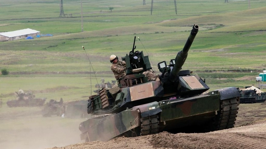 U.S. M1A2 Abrams tank moves to firing positions during joint military exercises at the Vaziani military base outside Tbilisi, Georgia, Wednesday, May 18, 2016. About 1,300 U.S., British and Georgian troops conducted joint exercises aimed at training the former Soviet republic's military for participation in the NATO Response Force. (AP Photo/Shakh Aivazov)