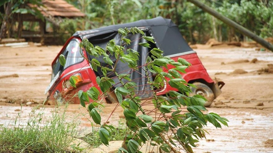 May 18, 2016: This photograph provided by Sri Lankan Red Cross shows an autorickshaw, a three wheeler vehicle partially submerged in mud after a massive landslide at Aranayaka in Kegalle District, about 45 miles north of Colombo, Sri Lanka.