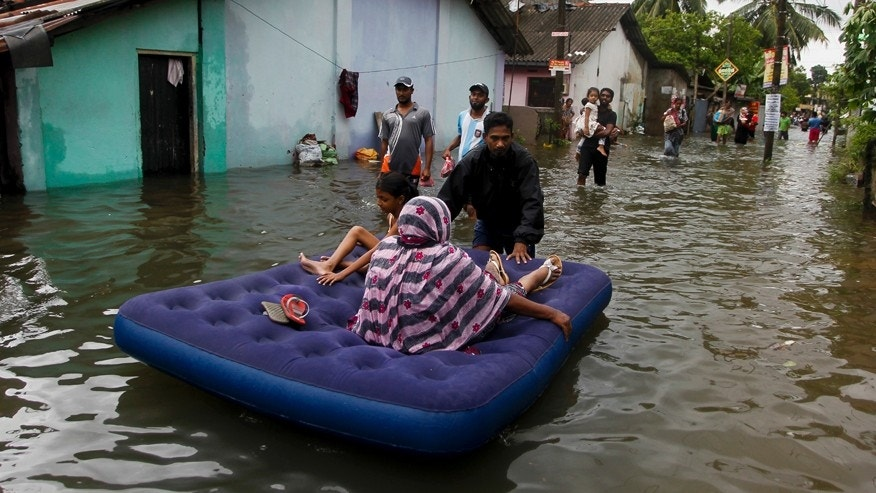May 17, 2016: An elderly Sri Lankan woman and a girl are shifted on a mattress at a flooded area in Colombo, Sri Lanka. The Disaster Management Center said that 114 homes have been destroyed and more than 137,000 people have been evacuated to safe locations as heavy rains continue.