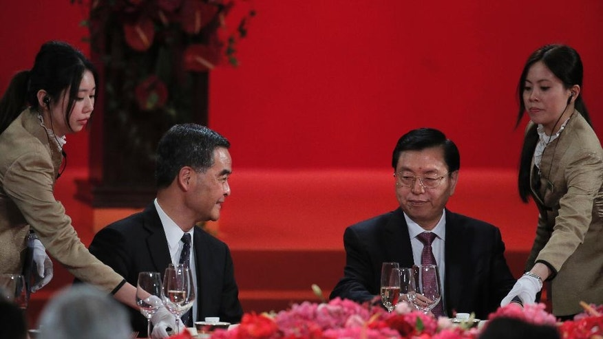 Hong Kong Chief Executive Leung Chun-ying, left, looks at Zhang Dejiang, right, chairman of China's National People's Congress, during a banquet in Hong Kong, Wednesday, May 18, 2016. Hong Kong authorities stepped up security for a top Chinese government official as he appeared at a business conference Wednesday, preventing pro-democracy protesters from approaching the venue. (AP Photo/Vincent Yu)