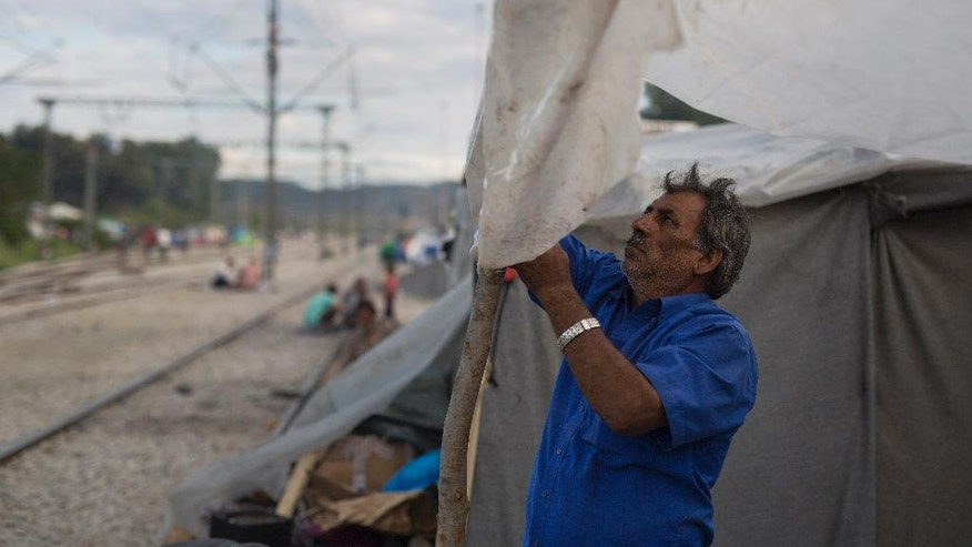 A Syrian man covers with a plastic sheet the entrance of his tent at a makeshift refugee camp on the northern Greek border point of Idomeni, Sunday, May 15, 2016. Thousands of stranded refugees and migrants have camped in Idomeni for months after the border was closed. (AP Photo/Petros Giannakouris)