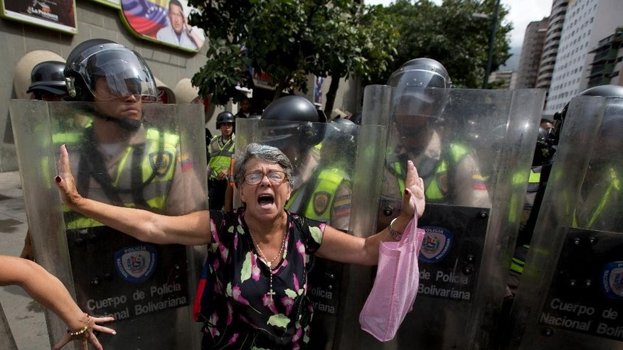 A demonstrator is blocked by Bolivarian National police during an anti-government march to the headquarters of the national electoral body, CNE, in Caracas, Venezuela, Wednesday, May 18, 2016. Opposition protesters were blocked from reaching the CNE as they demand the government allow it to pursue a recall referendum against Venezuela's President Nicolas Maduro. (AP Photo/Fernando Llano)