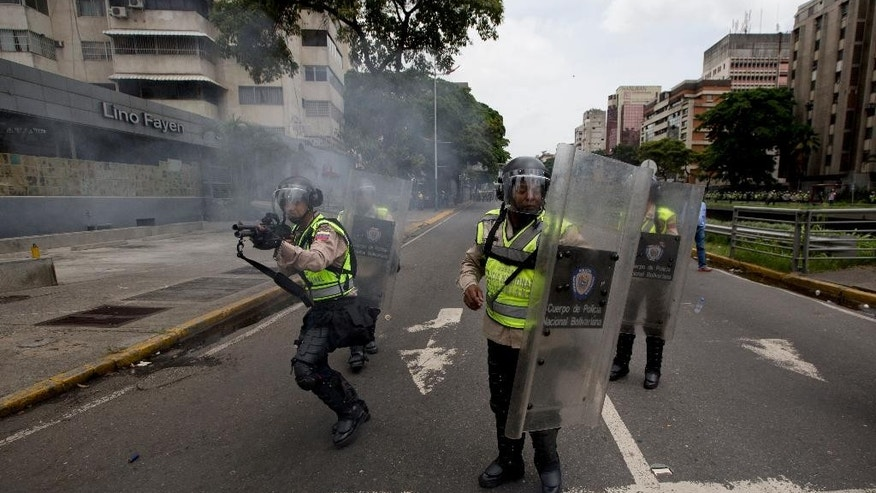 Bolivarian National police fire rubber bullets at anti-government demonstrators trying to march to the headquarters of the national electoral body, CNE, in Caracas, Venezuela, Wednesday, May 18, 2016. The opposition was blocked from marching to the CNE as they demand the government allow it to pursue a recall referendum against Venezuela's President Nicolas Maduro.  (AP Photo/Fernando Llano)