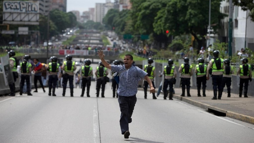 A demonstrator, who slipped past the barrier of Bolivarian National police, runs during an anti-government march toward the headquarters of the national electoral body, CNE, in Caracas, Venezuela, Wednesday, May 18, 2016. The opposition was blocked from marching to the CNE as they demand the government allow it to pursue a recall referendum against Venezuela's President Nicolas Maduro.  (AP Photo/Fernando Llano)