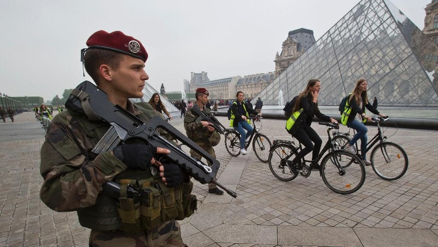 French soldier staff sergeant  Baudouin  patrols at the Louvre museum in Paris, Friday, May 13, 2016. The Associated Press was allowed to accompany a platoon from the French army's 1st Parachute Hussar Regiment as it demonstrated a typical patrol at the Louvre Museum in Paris. The AP was allowed only on condition that the soldiers involved be identified by their rank and first name. (AP Photo/Michel Euler)