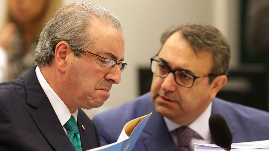 Brazil's former Lower House President Eduardo Cunha, left, talks with his lawyer Marcelo Nobre as he testifies before the Parliamentary Commission of Inquiry in connection with the so-called Car Wash probe, at Congress in Brasilia, Brazil, Thursday, May 19, 2016. Investigators uncovered a multi-billion dollar kickback scheme centered on the state oil company Petrobras and dozens of the country's elites have been ensnared, from top lawmakers to businessmen. The Supreme Federal Tribunal recently removed Cunha from office. (AP Photo/Eraldo Peres)
