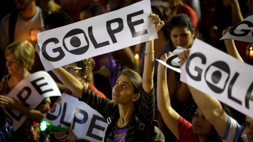 "FILE - In this May 10, 2016 file photo, a demonstrator holds a sign that reads in Portuguese; ""Coup"" during a protest against the impeachment proceedings of Brazil's President Dilma Rousseff, in Rio de Janeiro, Brazil. Analysts say that even if the suspended leader is deeply committed to fighting a process that she has long called a ìcoupî cooked up by power-hungry foes, she has few options. Rousseff and her left-leaning Workersí Party tried to combat impeachment at every implacable step and were repeatedly routed. (AP Photo/Silvia Izquierdo, File)"