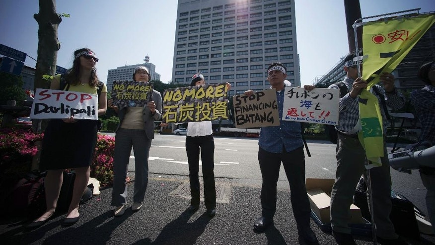 A group of people state a protest against climate change and coal investments, ahead of the G7 Finance Ministers and Central Bank Governors' Meeting, in front of the Ministry of Finance in Tokyo, Thursday, May 19, 2016. The G7 Finance Ministers and Central Bank Governors' Meeting is held on May 20-21 in Sendai, northern Japan. (AP Photo/Eugene Hoshiko)