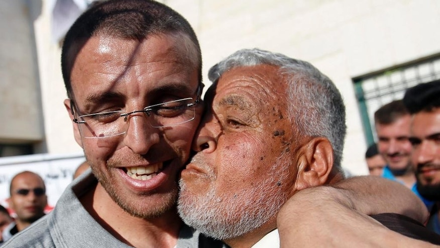 Palestinian journalist Mohammed al-Qeq, left is received by a relative on his arrival at the West Bank village of Dora, near Hebron, Thursday, May 19, 2016. The Israeli military said al-Qeq who ended a 94-day hunger strike in February has been released to his home in the West Bank. Al-Qeq went on hunger strike in November to win release from administrative detention, a practice that can keep some prisoners in custody without charges for an indefinite time. Israel says the detention is an important security tool to deter militant attacks. Israel said al-Qeq was involved in activities linked to the militant group Hamas. (AP Photo/Nasser Shiyoukhi)