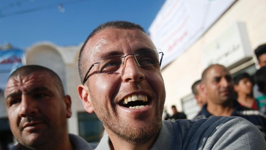 Palestinian journalist Mohammed al-Qeq is received by relatives on his arrival at the West Bank village of Dora, near Hebron, Thursday, May 19, 2016. The Israeli military said al-Qeq who ended a 94-day hunger strike in February has been released to his home in the West Bank. Al-Qeq went on hunger strike in November to win release from administrative detention, a practice that can keep some prisoners in custody without charges for an indefinite time. Israel says the detention is an important security tool to deter militant attacks. Israel said al-Qeq was involved in activities linked to the militant group Hamas. (AP Photo/Nasser Shiyoukhi)