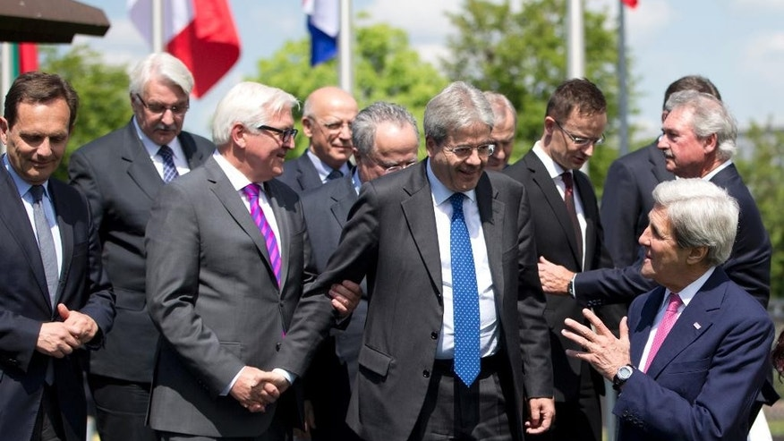 U.S. Secretary of State John Kerry, right, speaks with Italian Foreign Minister Paolo Gentiloni, center, and German Foreign Minister Frank-Walter Steinmeier, third left, during a group photo at NATO headquarters in Brussels on Thursday, May 19, 2016. NATO foreign ministers this week will discuss how the alliance can deal more effectively with security threats outside Europe, including by training the Iraqi military and cooperating with the European Union to choke off people-smuggling operations in the central Mediterranean. (AP Photo/Virginia Mayo)