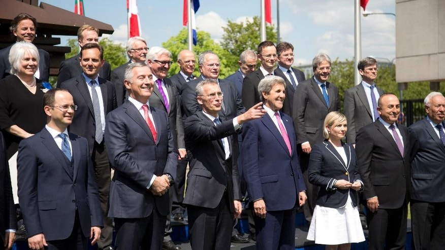 U.S. Secretary of State John Kerry, center right, stands with NATO Secretary General Jens Stoltenberg, center left, and other NATO foreign ministers during a group photo at NATO headquarters in Brussels on Thursday, May 19, 2016. NATO foreign ministers this week will discuss how the alliance can deal more effectively with security threats outside Europe, including by training the Iraqi military and cooperating with the European Union to choke off people-smuggling operations in the central Mediterranean. (AP Photo/Virginia Mayo)
