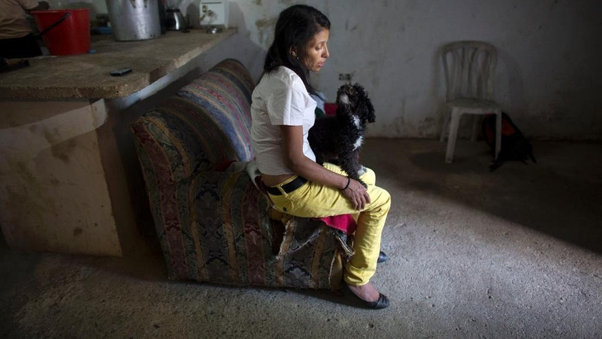 In this May 10, 2016 photo, Argelia Gamboa, Roberto Bernal's widow, sits on a sofa with a family pet, in a hillside slum in Caracas, Venezuela. A mob beat her husband unconscious and then burned him alive. Gamboa says her husband was so badly burned by the mob that she walked right past him when she rushed to the hospital. He died the next day. (AP Photo/Ariana Cubillos)