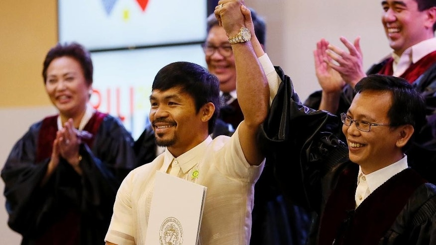 Filipino boxing great Manny Pacquiao holds his Certificate of Canvass as he is proclaimed the Seventh Senator by Commissioner Christopher Lim, right, in ceremony at the Commission on Elections Thursday, May 19, 2016 in suburban Pasay city south of Manila, Philippines. Pacquiao has won a seat in the Philippine Senate based on an unofficial count bringing him closer to a possible crack at the presidency. Pacquiao said he will retire from boxing to become a full-time politician. (AP Photo/Bullit Marquez)