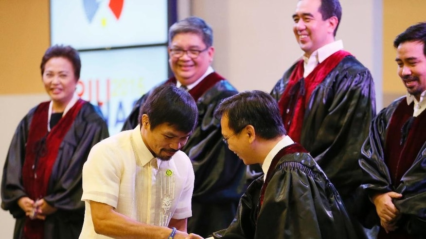 Filipino boxing great Manny Pacquiao receives his Certificate of Canvass from Commissioner Christopher Lim, right, as he is proclaimed the Seventh Senator in ceremony at the Commission on Elections Thursday, May 19, 2016 in suburban Pasay city south of Manila, Philippines. Pacquiao has won a seat in the Philippine Senate based on an unofficial count bringing him closer to a possible crack at the presidency. Pacquiao said he will retire from boxing to become a full-time politician. (AP Photo/Bullit Marquez)