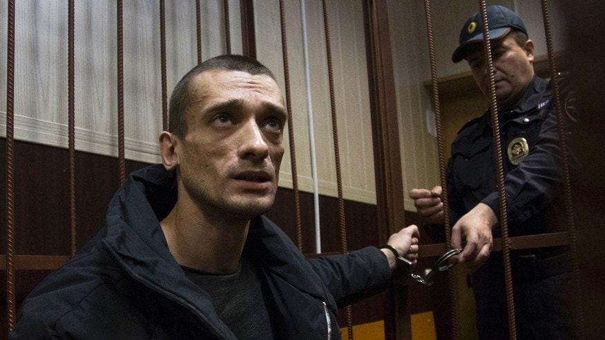 March 31, 2016: Russian artist Petr Pavlensky speaks to journalists as he sits in a cage in court room in Moscow, Russia.