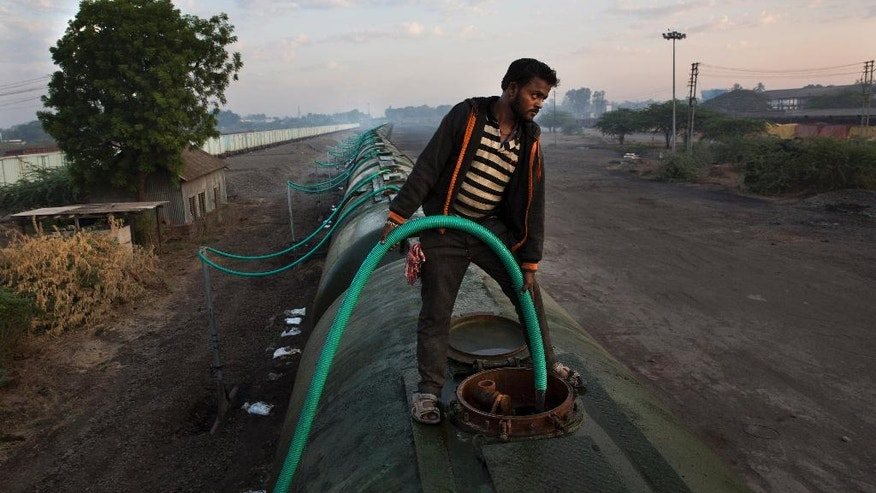 """In this May 9, 2016, photo, a worker fills water in one of the many tanks of the Jaldoot water train at the Miraj railway station, Miraj, 340 kilometers (212 miles) from Latur, in the Indian state of Maharashtra. Many trains pull into Latur's railroad station but none is as eagerly awaited as this train that pulls into the parched town in the dead of the night. That train called """"Jaldoot"""" or the Messenger of Water brings millions of liters of the precious liquid that the drought-plagued central Indian district so desperately needs. (AP Photo/Manish Swarup)"""