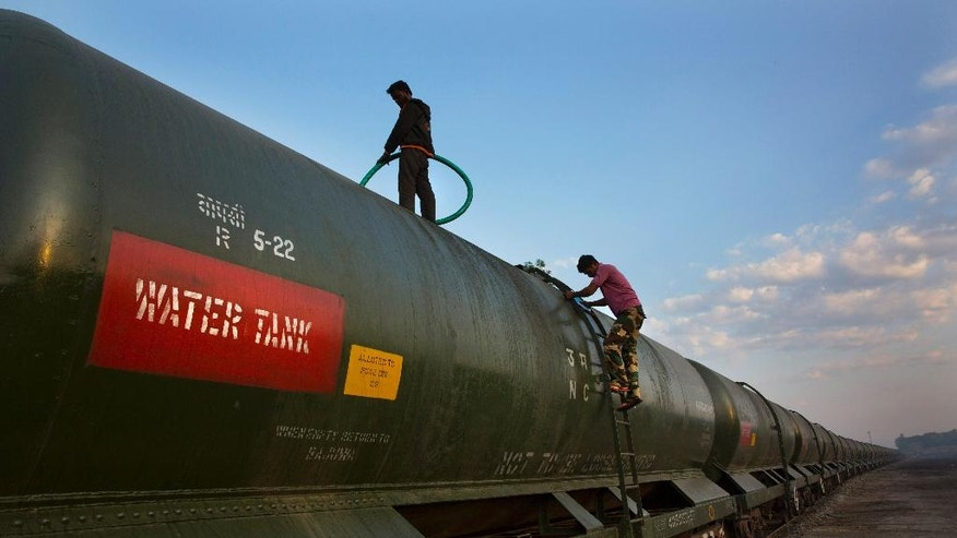 """In this May 9, 2016, photo, workers fill a water tank on the Jaldoot water train at the Miraj railway station, Miraj, 340 kilometers (211 miles) from Latur, in the Indian state of Maharashtra. Many trains pull into Latur's railroad station but none is as eagerly awaited as this train that pulls into the parched town in the dead of the night. That train called """"Jaldoot"""" or the Messenger of Water brings millions of liters of the precious liquid that the drought-plagued central Indian district so desperately needs. (AP Photo/Manish Swarup)"""