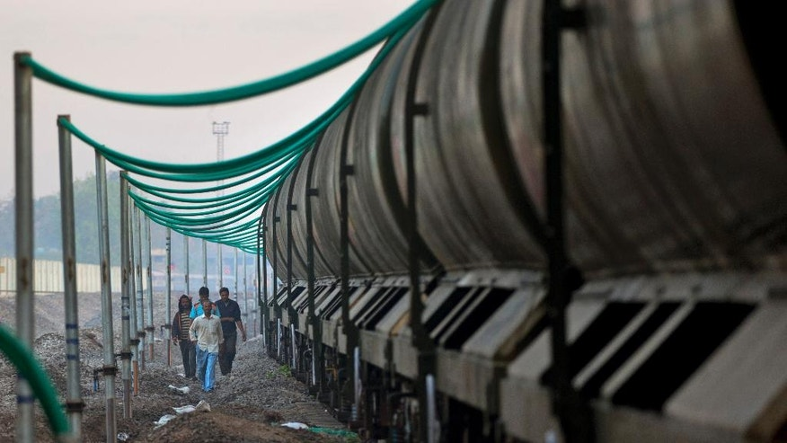 """In this May 9, 2016, photo, Indian workers check water pipes attached to the carriages of the Jaldoot water train at the Miraj railway station, Miraj, 340 kilometers (211 miles) from Latur, in the Indian state of Maharashtra. Many trains pull into Latur's railroad station but none is as eagerly awaited as this train that pulls into the parched town in the dead of the night. That train called """"Jaldoot"""" or the Messenger of Water brings millions of liters of the precious liquid that the drought-plagued central Indian district so desperately needs. (AP Photo/Manish Swarup)"""