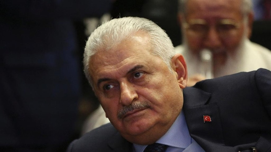 In this Thursday, May 12, 2016 photo, Binali Yildirim, Turkey's Transportation Minister and founding member of Turkey's governing AKP party, participates in a meeting in Ankara, Turkey.  It is announced Thursday May 19, 2016, Yildirim will stand unopposed for the party leadership and thereby automatically become Prime Minister at an extraordinary meeting to be held Sunday in Ankara. The shake up comes after Prime Minister Ahmet Davutoglu stepped down on May 4.(AP Photo/Burhan Ozbilici)