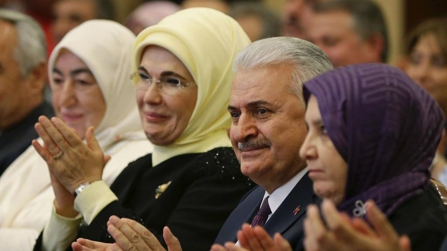 In this Tuesday, May 17, 2016 photo, Binali Yildirim, centre,Turkey's Transportation Minister, sitting next to Emine Erdogan, 2nd left, the wife of Turkey's President Recep Tayyip Erdogan, applauds during a meeting in Ankara, Turkey.  It is announced Thursday May 19, 2016, Yildirim will stand unopposed for the party leadership and thereby automatically become Prime Minister at an extraordinary meeting to be held Sunday in Ankara.  The shake up comes after Prime Minister Ahmet Davutoglu stepped down on May 4 over differences with president Erdogan.(Murat Cetinmuhurdar/Press Presidency Press Service via AP, Pool)