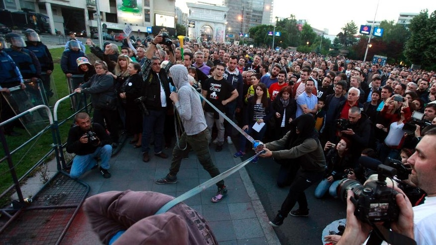 Protestors use an improvised slingshot to throw balloons filled with colored paint toward the Parliament building, during an anti-government protest in Skopje, Macedonia, Wednesday, May 18, 2016. Macedonia's parliament voted in an urgent session Wednesday to delay an early general election scheduled for June 5, after a top court temporarily suspended all electoral activities. (AP Photo/Boris Grdanoski)