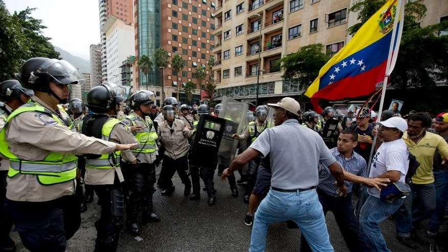 Anti-government demonstrators try to break through a barrier of Bolivarian National Police in an effort to reach the headquarters of the national electoral body, CNE, in Caracas, Venezuela, Wednesday, May 18, 2016. The opposition was blocked from marching to the CNE to demand the government allow it to pursue a recall referendum against Venezuela's President Nicolas Maduro. (AP Photo/Fernando Llano)