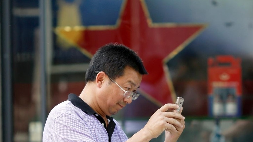 A man uses his mobile phone near a red star along a retail shop in Beijing Friday, May 20, 2016. China's government fabricates and posts several hundred million social media posts a year to influence public opinion about the country, according to a new paper by U.S. researchers examining one of the most opaque aspects of the Communist Party's rule. (AP Photo/Ng Han Guan)