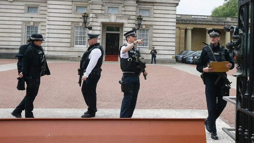 Armed police officers work at the main gate of Buckingham Palace in London, Thursday, May 19, 2016. British police say they have arrested a man who scaled a wall and got into the grounds of Buckingham Palace. The Metropolitan Police force says a 41-year-old man was detained in the palace grounds Wednesday evening on suspicion of trespassing on a protected site. (AP Photo/Kirsty Wigglesworth)
