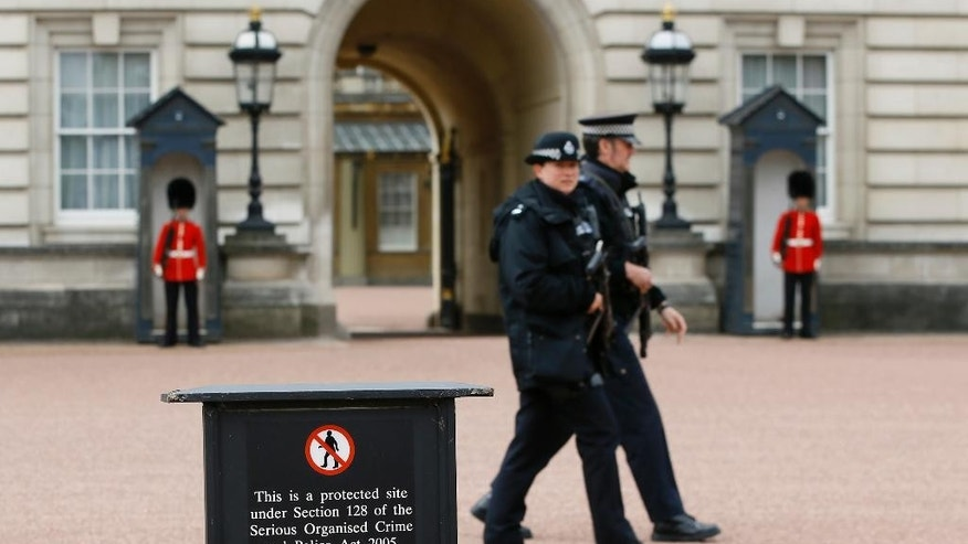 Armed police officers patrol in the grounds of Buckingham Palace in London, Thursday, May 19, 2016. British police say they have arrested a man who scaled a wall and got into the grounds of Buckingham Palace. The Metropolitan Police force says a 41-year-old man was detained in the palace grounds Wednesday evening on suspicion of trespassing on a protected site. (AP Photo/Kirsty Wigglesworth)