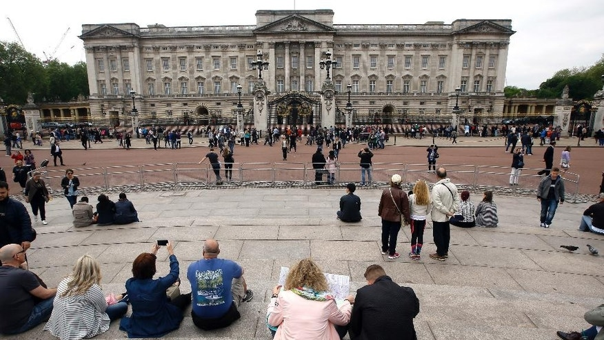 Tourists around Buckingham Palace in London, Thursday, May 19, 2016. British police say they have arrested a man who scaled a wall and got into the grounds of Buckingham Palace. The Metropolitan Police force says a 41-year-old man was detained in the palace grounds Wednesday evening on suspicion of trespassing on a protected site. (AP Photo/Kirsty Wigglesworth)
