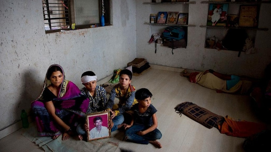 In this May 11, 2016, photo, Shima Pandit Agee, left, wife of Srikrishna Pandit Agee who committed suicide on May 9, 2016, holds the pictures of her husband as she sits with her sons Husikesh Agee, second left, Nitin Agee and daughter Aksara Agee in mourning in their home in village Devadi, one of the drought affected region in Marathwada, in the Indian state of Maharashtra. Failed monsoons play havoc with millions of farmers in central India leading to crippling poverty and soaring suicides. Some 400 farmers have killed themselves so far this year in the parched Marathwada region, which is home to about 19 million people. (AP Photo/Manish Swarup)
