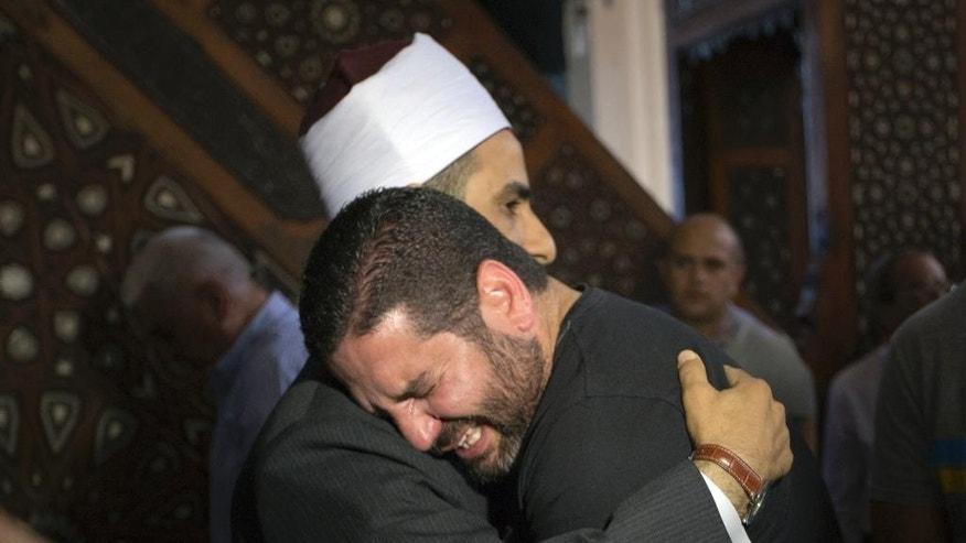 The Imam of al Thawrah Mosque, Samir Abdel Bary, gives condolences to film director Osman Abu Laban, center, who lost four relatives, all victims of Thursday's EgyptAir plane crash, following prayers for the dead, at al Thawrah Mosque, in Cairo, Egypt, Friday, May 20, 2016. The Airbus A320 plane was flying from Paris to Cairo when it disappeared early Thursday over the sea. (AP Photo/Amr Nabil)