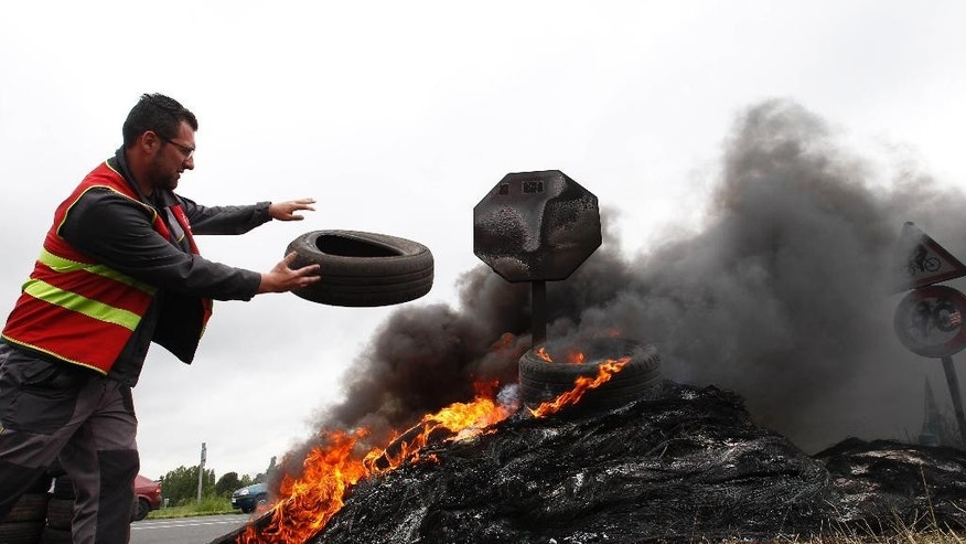 A CGT union member burns tyros at the blockade of a fuel depot in Douchy-les-Mines, northern France, Friday, May 20, 2016. Junior minister for Transports said 20 percent of gas stations in north-western France are closed Friday due to protests against a labor law that have disrupted the country's fuel supplies. CGT stands for General Confederation for Work.  (AP Photo/Michel Spingler)