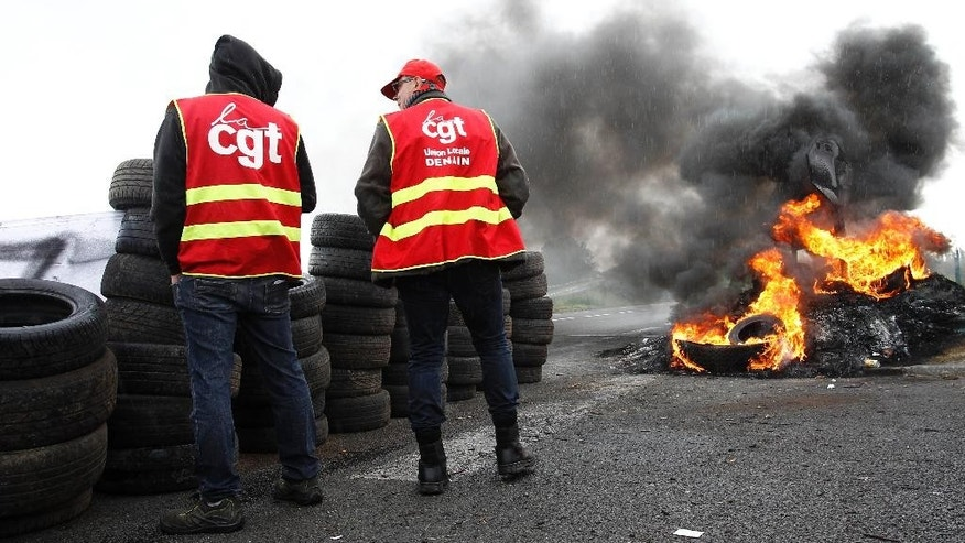 CGT union members stand near burning tyres at the blockade of a fuel depot in Douchy-les-Mines, northern France, Friday, May 20, 2016. Junior minister for Transports said 20 percent of gas stations in north-western France are closed Friday due to protests against a labor law that have disrupted the country's fuel supplies. CGT stands for General Confederation for Work.  (AP Photo/Michel Spingler)