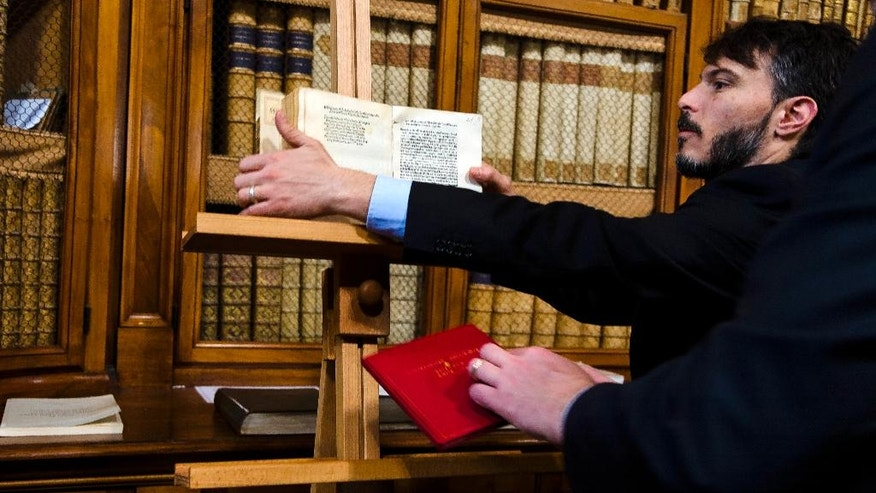 Italian Carabinieri officers remove a book, bottom, reproducing a reprinted copy of Christopher Columbus original letter written in 1493 about the discovery of the New World,  and another book, top, reproducing a fake of the reprinted copy, at the end of a press conference in Rome, Wednesday, May 18, 2016. The United States has returned to Italy a letter written by Christopher Columbus that was stolen from a Florence library, unwittingly acquired by the Library of Congress, and replaced with a forgery that no one noticed until a few years ago. (AP Photo/Domenico Stinellis)