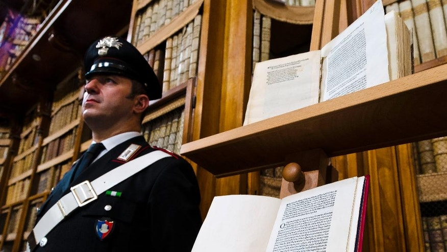 A Carabinieri policeman stands, Wednesday, May 18, 2016, next to a book, bottom, reproducing a letter written by Christopher Columbus in 1493 about his discovery of the New World that had been replaced at Florence's Riccardiana library with a forgery, at top, that no one noticed until a few years ago, during a press conference in Rome. (AP Photo/Domenico Stinellis)