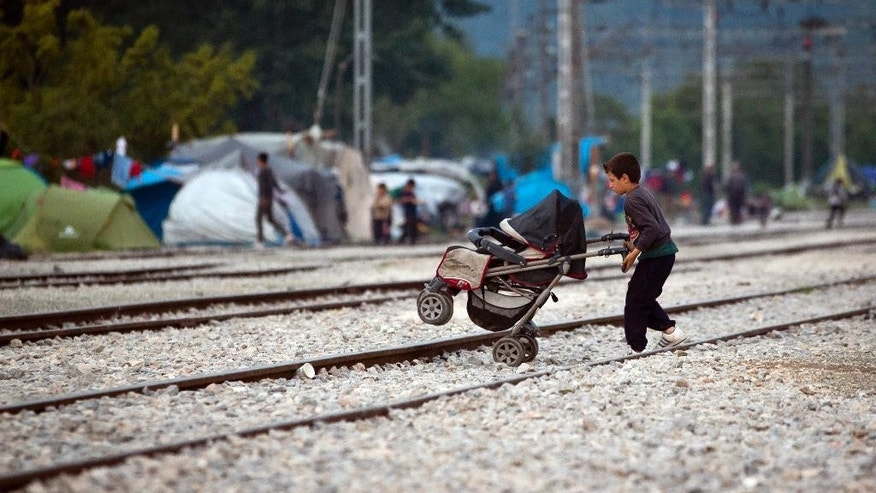 A boy pushes a stroller over railway tracks at the migrants camp in Idomeni, Greece, Thursday, May 19, 2016.  Thousands of stranded refugees and migrants have camped in Idomeni for months after the border was closed. (AP Photo/Darko Bandic)