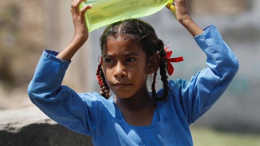 An Indian school girl cools her head with a cold water bottle in Jammu, India, Thursday, May 19, 2016. Scorching summer temperatures, hovering well over 40 degrees Celsius, (104 Fahrenheit) are making life extremely tough for millions of people across north India. (AP Photo/Channi Anand)