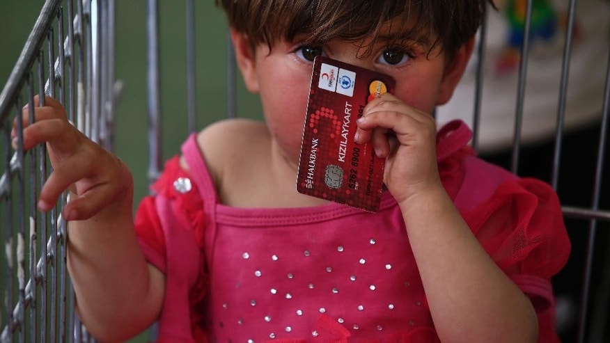 In this Monday, May 16, 2016 photo, two-year old Maria al-Ali, a Syrian refugee child, holding a debit card provided by the World Food Program, to take care partially of the family's groceries, sits in a trolley at a supermarket in the city of Gaziantep, southeastern Turkey. Known as e-food, this voucher system has emerged as an innovative and easily scalable tool of humanitarian aid at a time the international community is struggling to achieve more with less. Turkey, host to the largest refugee population in the world, including 2.7 million Syrians, is on the front line of the crisis. (AP Photo/Lefteris Pitarakis)