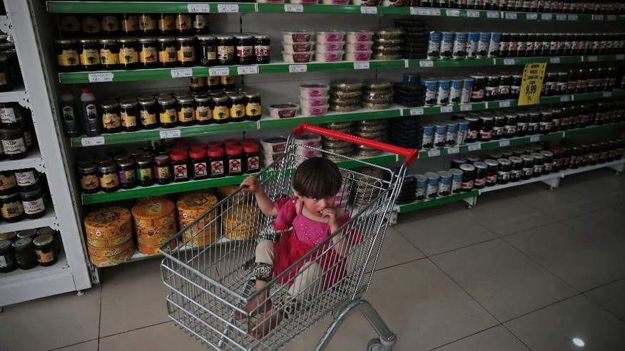 In this Monday, May 16, 2016 photo, two-year old Maria al-Ali, a Syrian refugee child, sits in a trolley at a supermarket in the city of Gaziantep, southeastern Turkey. Maria's mother Huda is using a debit card provided by the World Food Program, to take care partially of the family's groceries. Known as e-food, this voucher system has emerged as an innovative and easily scalable tool of humanitarian aid at a time the international community is struggling to achieve more with less. Turkey, host to the largest refugee population in the world, including 2.7 million Syrians, is on the front line of the crisis. (AP Photo/Lefteris Pitarakis)
