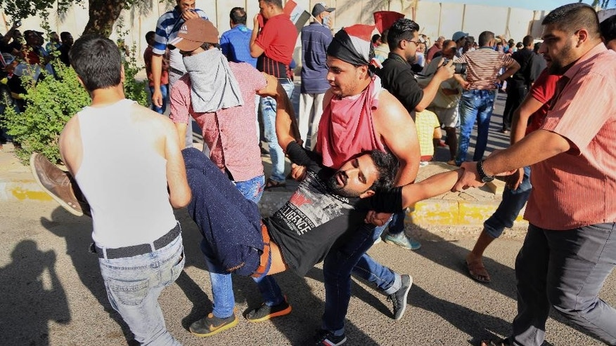 An injured protester is rushed to treatment outside Baghdad's highly fortified Green Zone Friday, May 20, 2016. Iraqi security forces have fired tear gas and gunshots in the air as thousands of Shiite protesters stormed Baghdad's heavily secured Green Zone, rushing toward the prime minister's office and parliament building. (AP Photo/Karim Kadim)